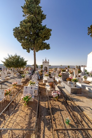 funerary: Crato, Portugal. December 12, 2015: Poor people graves in a typical Catholic cemetery with the graves decorated with flowers in the interior south of Portugal.