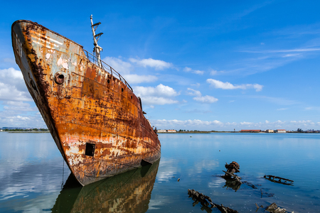 old ship: Old ship run aground and rusting in the shore. Seixal, Portugal.