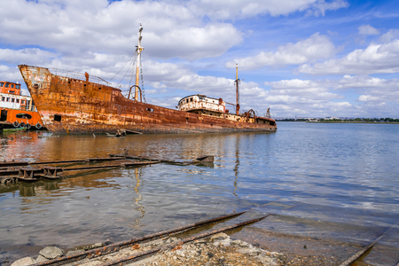 scrap: Old ship run aground and rusting in the shore. Seixal, Portugal.