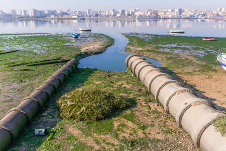 cesspool: Two open air sewer pipes draining to the Seixal Bay, a Tagus River branch near Lisbon, Portugal.