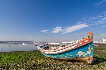 beached: Small, old traditional boat in Seixal bay. Portugal. Stock Photo