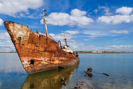 aground: Old ship run aground and rusting in the shore. Seixal, Portugal.