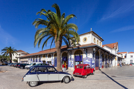 ribatejo: Santarem, Portugal. September 10, 2015: The Farmers Market of Santarem with two classic European cars, the Citroen Dyane (gray) and the Citroen 2cv (red) parked in front of it.