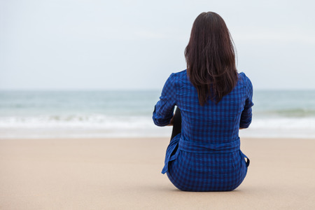 melancholy: Lonely and depressed woman sitting on the sand of a deserted beach and watching the sea on an Autumn day.