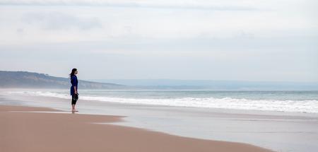 persona triste: La mujer sola y deprimida mirando el mar en una playa desierta en un día de otoño.