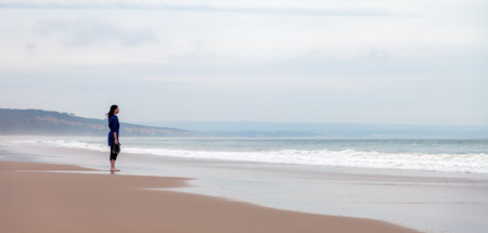 solitude: Lonely and depressed woman watching the sea in a deserted beach on an Autumn day.