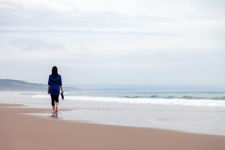 Jonge vrouw lopen weg alleen in een verlaten strand op een dag van de Herfst. Stockfoto