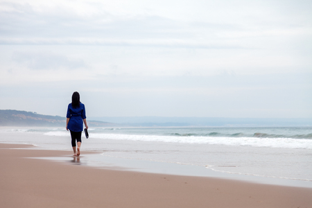 autumn young: Young woman walking away alone in a deserted beach on an Autumn day.