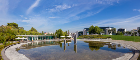 specular: Lisbon, Portugal - October 19, 2016: The Amalia Rodrigues Garden with a pond creating a specular reflection of an open air cafe.