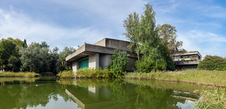 specular: Lisbon, Portugal - October 19, 2016: The auditorium seen across the lake in the garden of the Calouste Gulbenkian foundation. A very popular urban park open to the public. Editorial