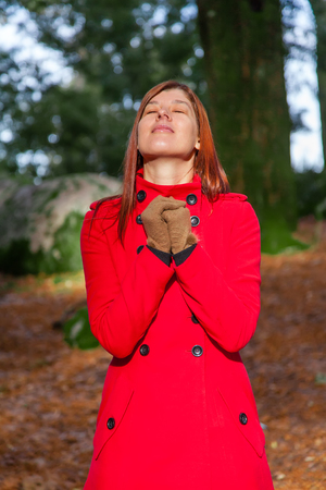 warmness: Woman on a forest praying and enjoying the warmth of the winter sunlight, wearing a red long coat
