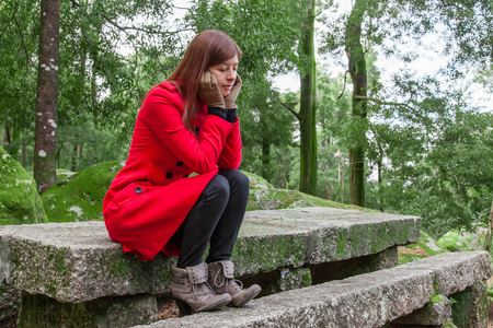 overcoat: Young woman feeling depressed sitting on a stone table and bench on a forest wearing a red overcoat during winter