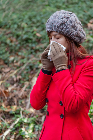 handkerchief: Young woman suffering from a cold, flu or allergies blowing her nose on a white paper handkerchief during winter Stock Photo