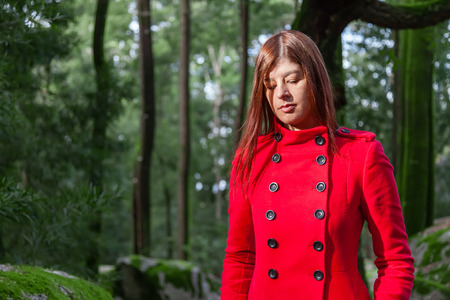 long depression: Young woman feeling sad and depressed walking on a forest wearing a red long coat during winter