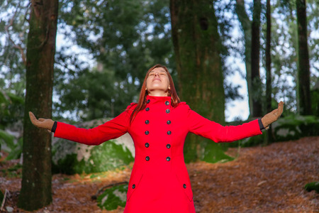 warmness: Woman enjoying the warmth of the winter sunlight on a forest wearing a red long coat