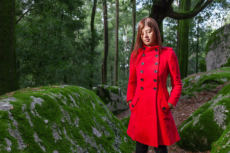 Young woman feeling sad and depressed walking on a forest wearing a red long coat during winter