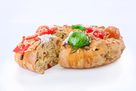 Sliced Bolo Rei (King Cake), the traditional Portuguese Christmas cake, made with candied fruits, isolated on white background Stock Photo