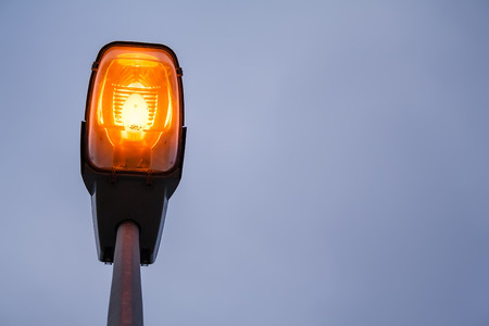Lit modern streetlamp at evening or early night with an orange bulb and sky with clouds Stock Photo