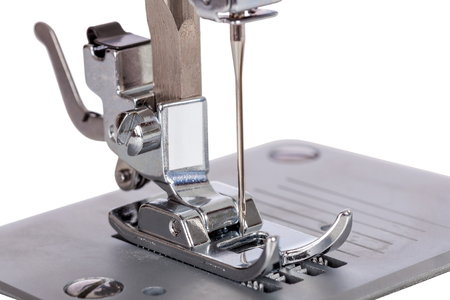 presser: Close up macro detail of the needle, plate, foot and transporter of an electric sewing machine