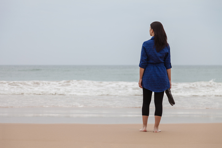 Lonely and depressed woman standing in front of the sea in a deserted beach on an Autumn day. Stock Photo