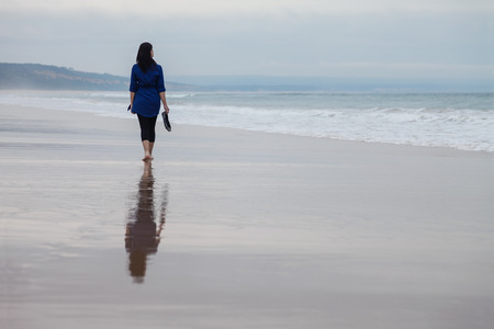 Young woman walking alone in a deserted beach reflected on the wet sand on an Autumn day. Stock Photo