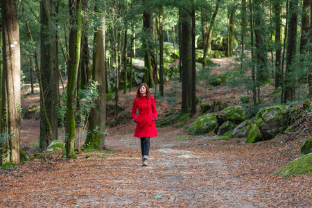 Young woman walking alone on a forest dirt path wearing a red overcoat on a cold winter day Stock Photo