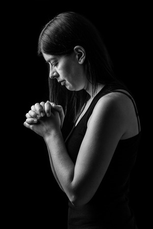 Faithful woman praying, hands folded in worship to god with head down and eyes closed in religious fervor, on a black background. Concept for religion, faith, prayer and spirituality. Stock Photo