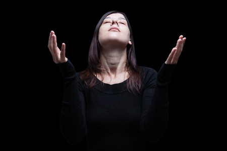 Mourning woman praying, with arms outstretched in worship to god, head up and eyes closed in suffer, on black background. Concept for religion, faith, prayer, grief, mourn, pain, depression. Stock Photo - 88203534