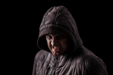 Very angry and aggressive man hiding in the shadows, with the face partly hidden with the hood, and standing in the darkness