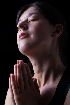 Low key of a happy faithful woman praying and smiling in happiness, bliss and peace, feeling inspired with the presence of god and his grace. Hands folded in worship, head up, eyes closed, black background. Stock Photo