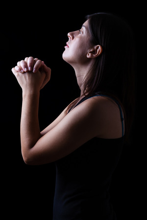 Faithful woman praying in worship to god looking up in hope, with hands folded and religious fervor on a black background. Concept for religion, faith, prayer and spirituality. Stock Photo