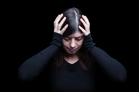 Distressed, woman holding the head with the hands, on a black or dark background