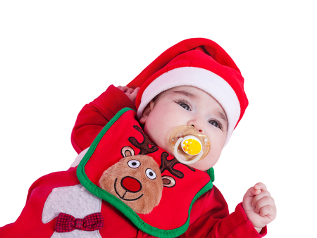 Baby girl with pacifier or dummy, red babygrow or onesie, Rudolph reindeer bib, Santa Claus hat for Christmas. Isolated white background. Four months
