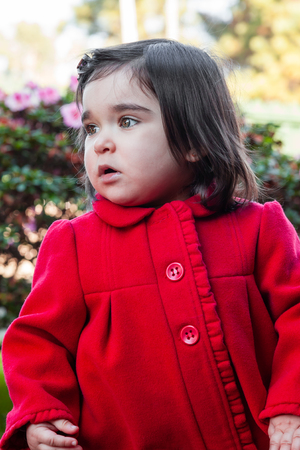 Cute, pretty, happy and fashionable toddler baby girl, wearing a good fashion red long coat or overcoat on a cold winter day in a garden. 18 or eighteen months old