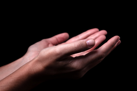 Female hands praying with palms up arms outstretched. Black background. Close up of woman hand. Concept for prayer, faith, religion, religious, worship Stock Photo