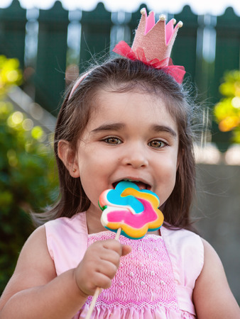 Happy baby toddler girl eating and biting a large colorful lollipop dressed in pink dress as princess or queen with crown, playing outdoor in garden