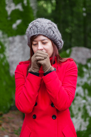 Young woman shivering with cold and blowing hot air to the hands on a forest wearing a red long coat or overcoat, a beanie and gloves during winter 스톡 콘텐츠