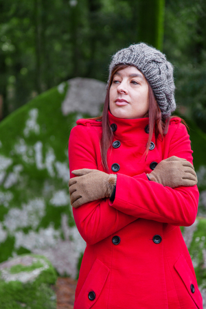Young woman lost on a forest shivering with cold and embracing or holding herself, wearing a red long coat or overcoat, a beanie and gloves during fall, autumn or winter