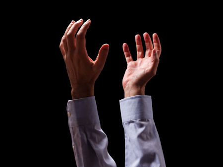 Male arms and hands raised and outstretched in the air to god. Man praying, begging, pleading imploring or supplicating. Black background. Businessman with Christian Catholic religious faith