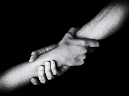 Man die vrouw redt, redt en helpt door de onderarm vast te houden of te grijpen. Mannelijke hand en arm trekken vrouw uit. Concept van redding, liefde, vriendschap, ondersteuning, teamwerk, partnerschap, bereiken, paar Stockfoto