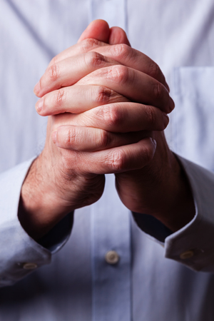 Close up or closeup of hands of faithful mature man praying. Hands folded, interlaced fingers in worship to god. Concept for religion, faith, prayer and spirituality.