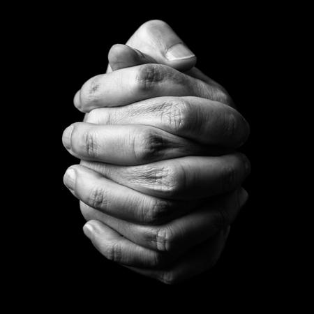 Chave de baixo, close-up das mãos de um homem maduro fiel orando, mãos dobradas, entrelaçadas dedos em adoração a Deus. Fundo preto isolado. Conceito de religião, fé, oração e espiritualidade.