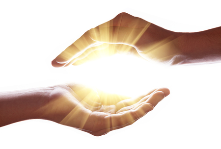 Woman hands protecting and containing bright, glowing, radiant, shining light. Emitting rays or beams expanding of center. Religion, divine, heavenly, celestial concept. White background copy space Stock Photo