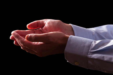 Mature male businessman hands together with empty palms up. Concept for man praying, prayer, faith, religion, religious, worship or giving, offering, begging, receiving. Black background. Foto de archivo