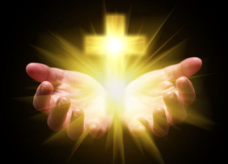 Hands cupped and holding or showing Cross or Crucifix with bright, glowing, shining light. Concept for Christian, Christianity, Catholic religion, divine, heavenly, celestial or god. Black background Stock Photo