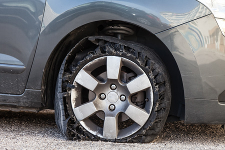 Destroyed blown out tire with exploded, shredded and damaged rubber on a modern suv automobile. Flat low profile tyre on an alloy rim, ripped open in pieces with visible interior. Stock Photo