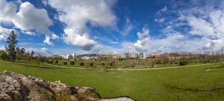 Panorama of a large empty green grass lawn field, with a view of the city in Parque da Devesa Urban Park. Blue sky with large white clouds. Vila Nova de Famalicao, Portugal