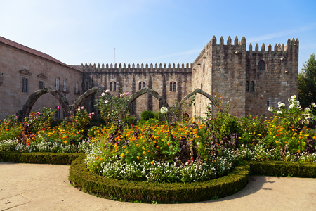 Braga, Portugal - October 16, 2015: Santa Barbara garden with the medieval Episcopal Palace of Braga in background.