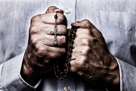African American male hands praying holding a beads rosary with Jesus Christ in the cross or Crucifix on black background. Mature Afro American man with Christian Catholic religious faith Stock Photo