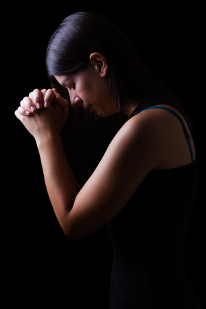 Faithful woman praying, hands folded in worship to god with head down and eyes closed in religious fervor, on a black background. Concept for religion, faith, prayer and spirituality. Standard-Bild